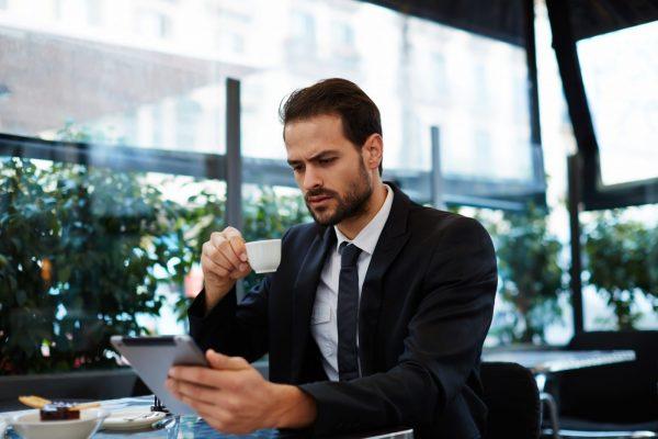Мужчина с планшетом и чашкой кофе в кафе