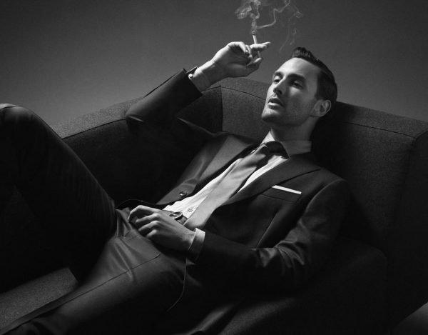 Мужчина с сигаретой лежит на диване