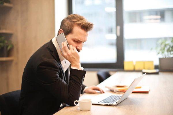 Мужчина с телефоном за ноутбуком