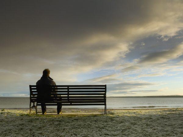 Мужчина сидит на скамейке на берегу реки