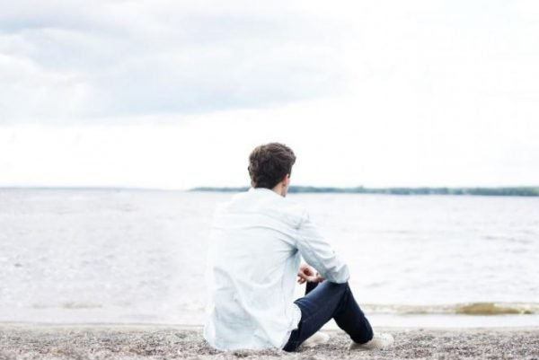 Мужчина сидит в одиночестве на берегу моря