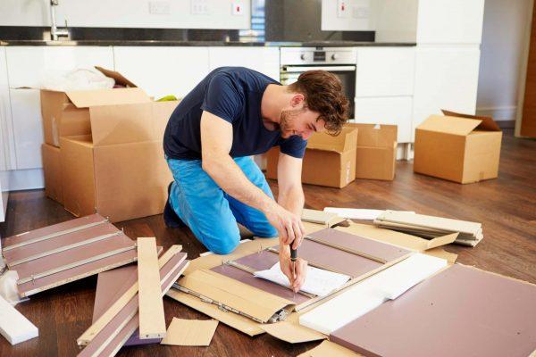 Мужчина собирает мебель