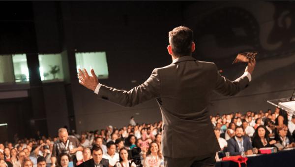 Мужчина стоит на сцене перед аудиторией