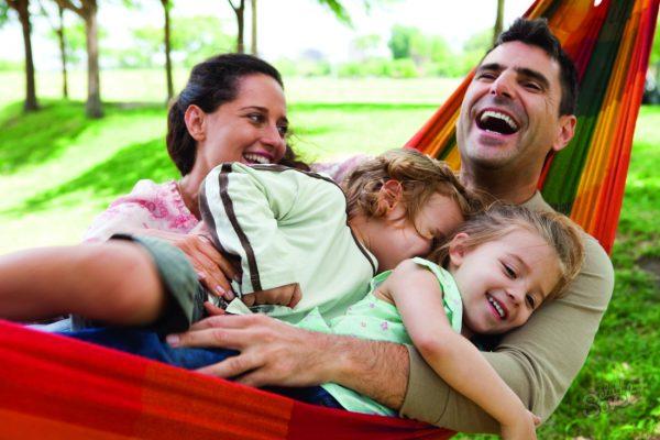 Мужчина в гамаке с детьми и женой на природе