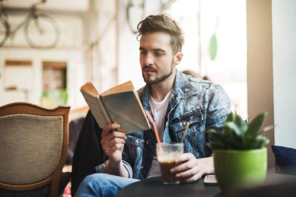 Мужчина в кафе читает книгу