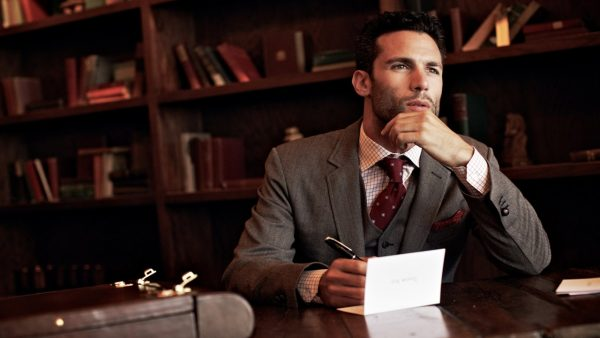 Мужчина в костюме что-то пишет на бумаге