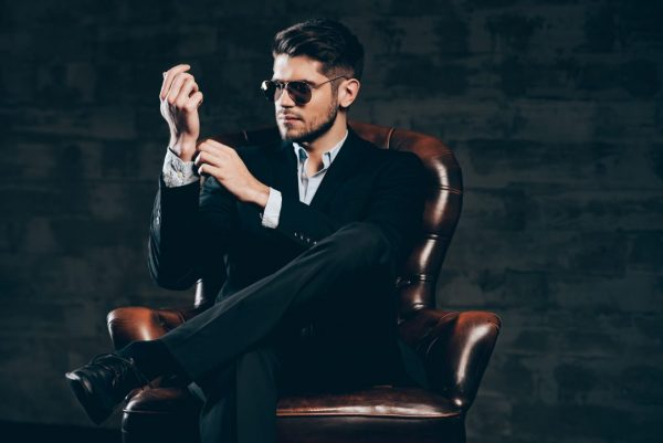 Мужчина в костюме и очках сидит в кресле
