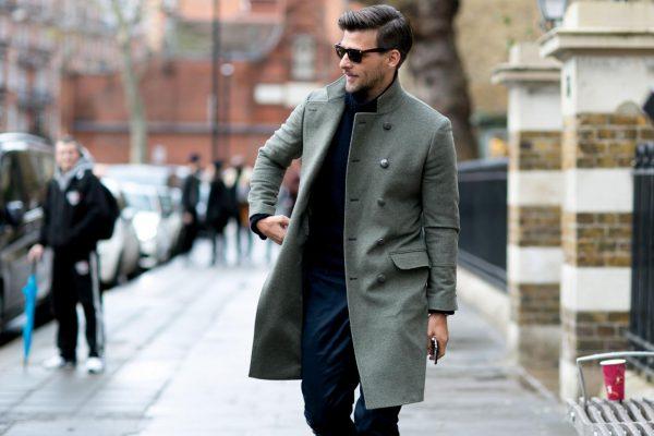 Мужчина в пальто и солнцезащитных очках идёт по улице