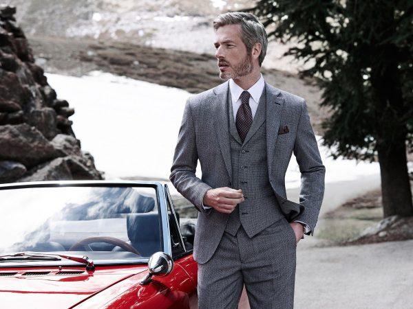 Мужчина в сером костюме стоит около автомобиля