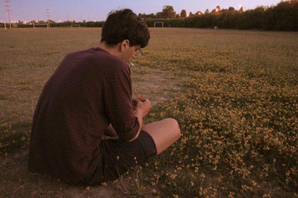 Парень сидит на траве
