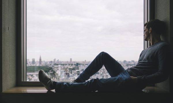 Парень сидит у окна