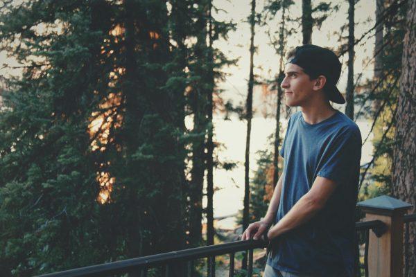 Парень смотрит на лес с балкона