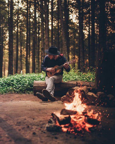 Парень в лесу играет на укулеле у костра