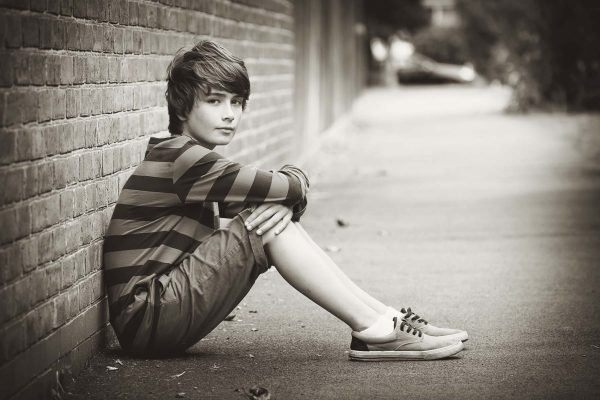 Подросток сидит на асфальте