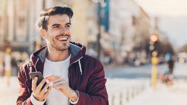 Улыбающийся молодой человек с телефоном в руках