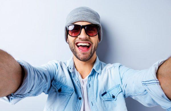 Улыбающийся парень в очках и шапке