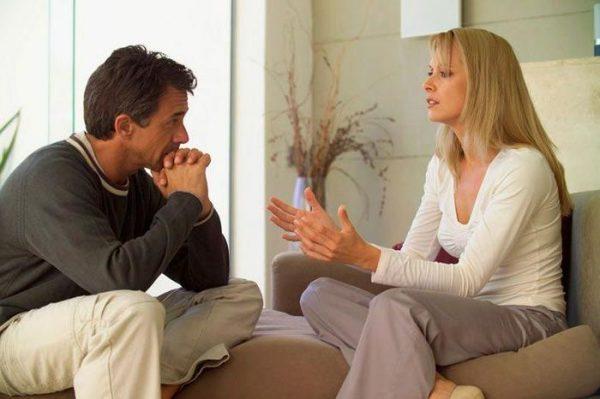 Мужчина и женщина разговаривают, сидя на диване