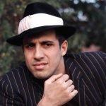 Адриано Челентано в полосатом костюме и шляпе