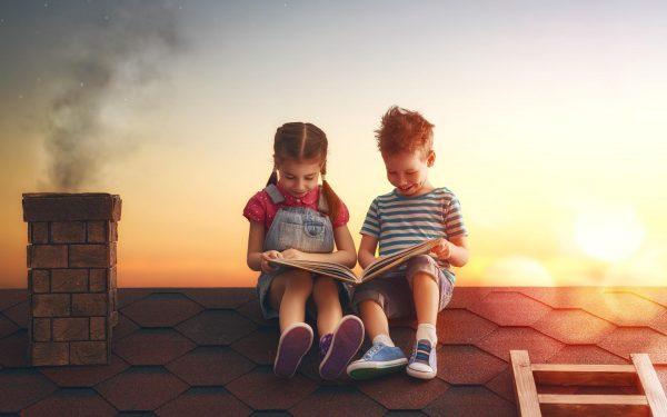 Девочка и мальчик читают книгу на крыше