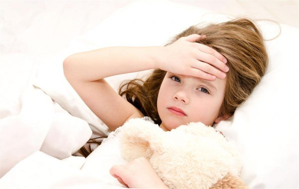 Девочка лежит в кровати с игрушкой