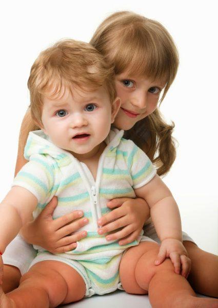 Девочка обнимает маленького мальчика