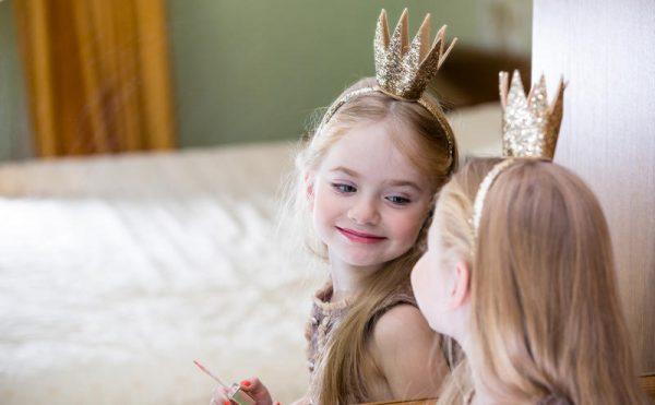 Девочка с короной любуется на себя в зеркало
