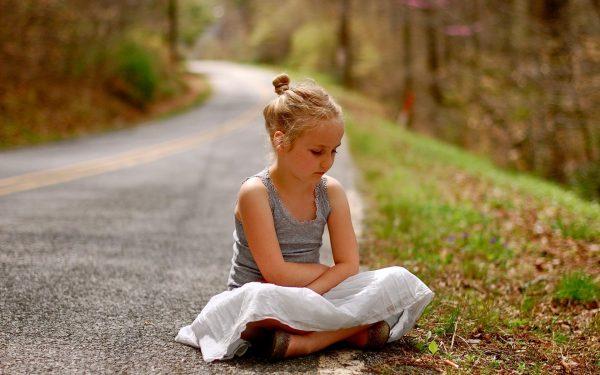Девочка сидит на дороге