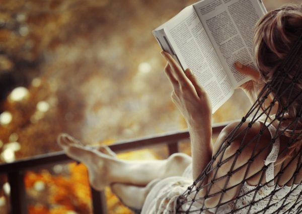 Девушка читает книгу, лёжа в гамаке