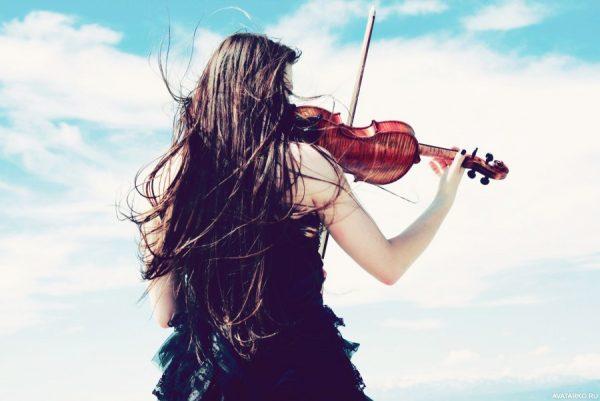 Девушка играет на скрипке на утёсе