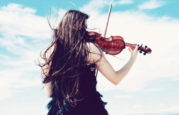 Девушка играет на скрипке у моря