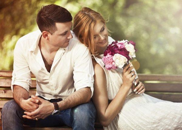 Девушка с букетом и парень на лавочке в парке
