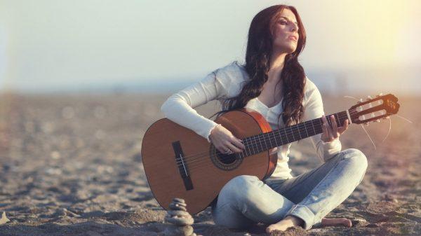 Девушка с гитарой сидит на песке
