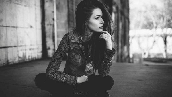 Девушка сидит на асфальте