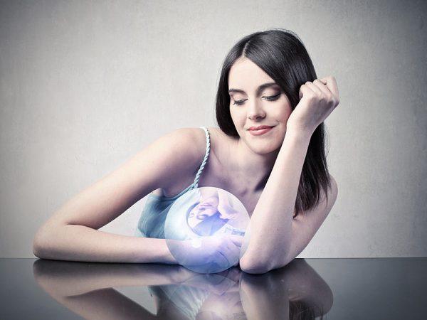 Девушка смотрит на волшебный шар