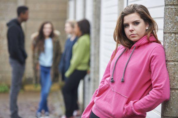 Девушка стоит в стороне от сверстников
