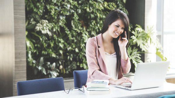 Девушка за ноутбуком разговаривает по телефону