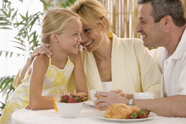Дочка с родителями сидят за столом