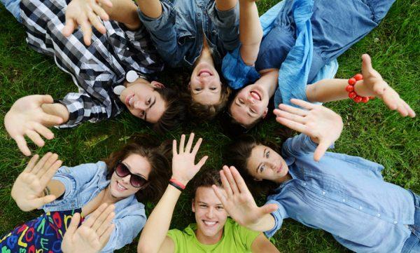 Дружеская компания лежит на траве