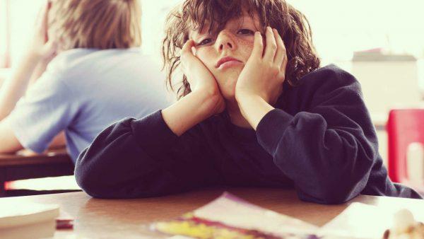 Недовольный мальчик сидит за столом