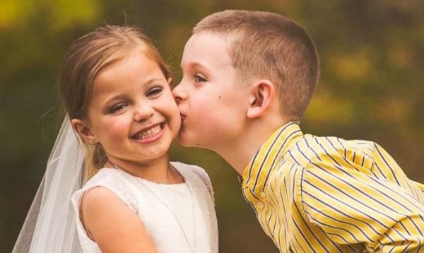 Мальчик целует девочку в щёку