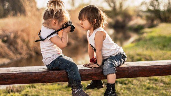 Мальчик и девочка сидят на бревне