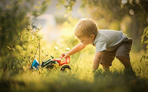 Мальчик играет на траве