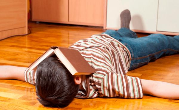 Мальчик лежит на полу с книгой на голове