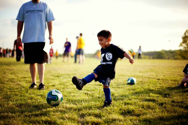 Мальчик пинает мяч
