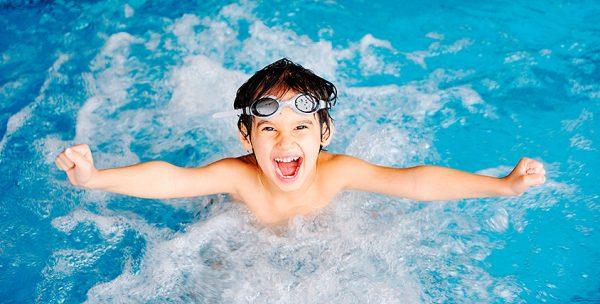 Мальчик плавает в бассейне