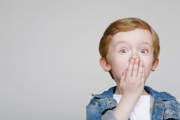 Мальчик прикрывает рот рукой