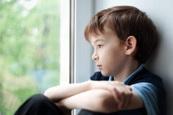 Мальчик сидит у окна