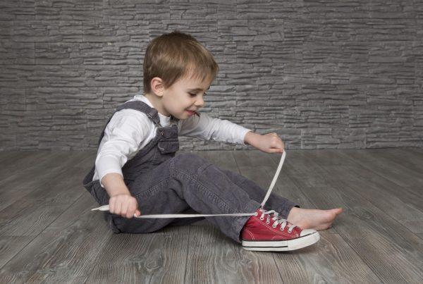 Мальчик завязывает шнурки