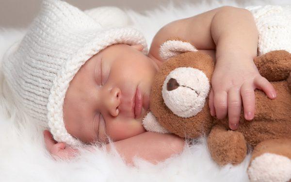 Младенец с игрушкой спит