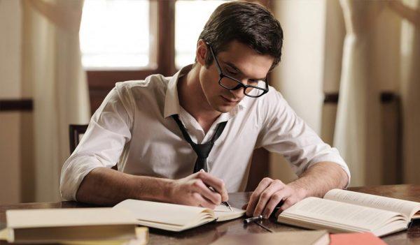 Мужчина что-то пишет, сидя за столом